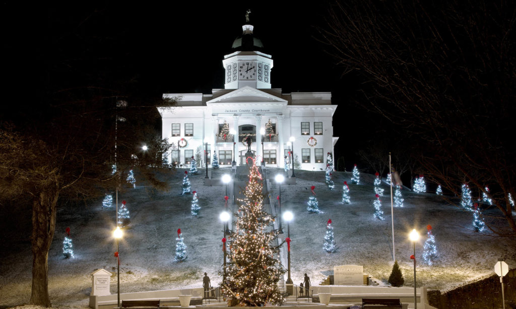 On a snowy December night is the old Jackson County Courthouse perched on a big hill at the end of Main Street, Downtown Sylva, NC. All these Christmas trees are placed on hill just this time of year. They are removed afterwards. The large tree in front is a water fountain most of the year.
